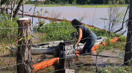 Diane wading in River behind Private Property sign