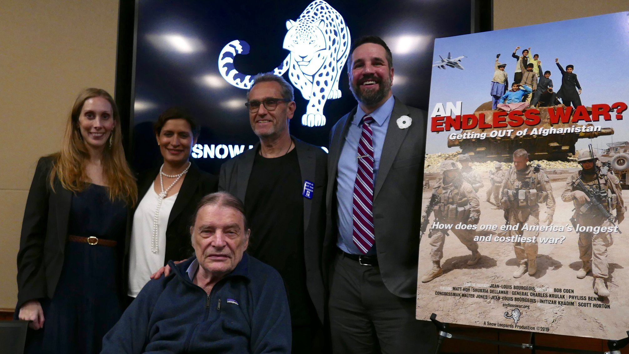 Image of Matt Hoh and others in front of an image from the film Endless War