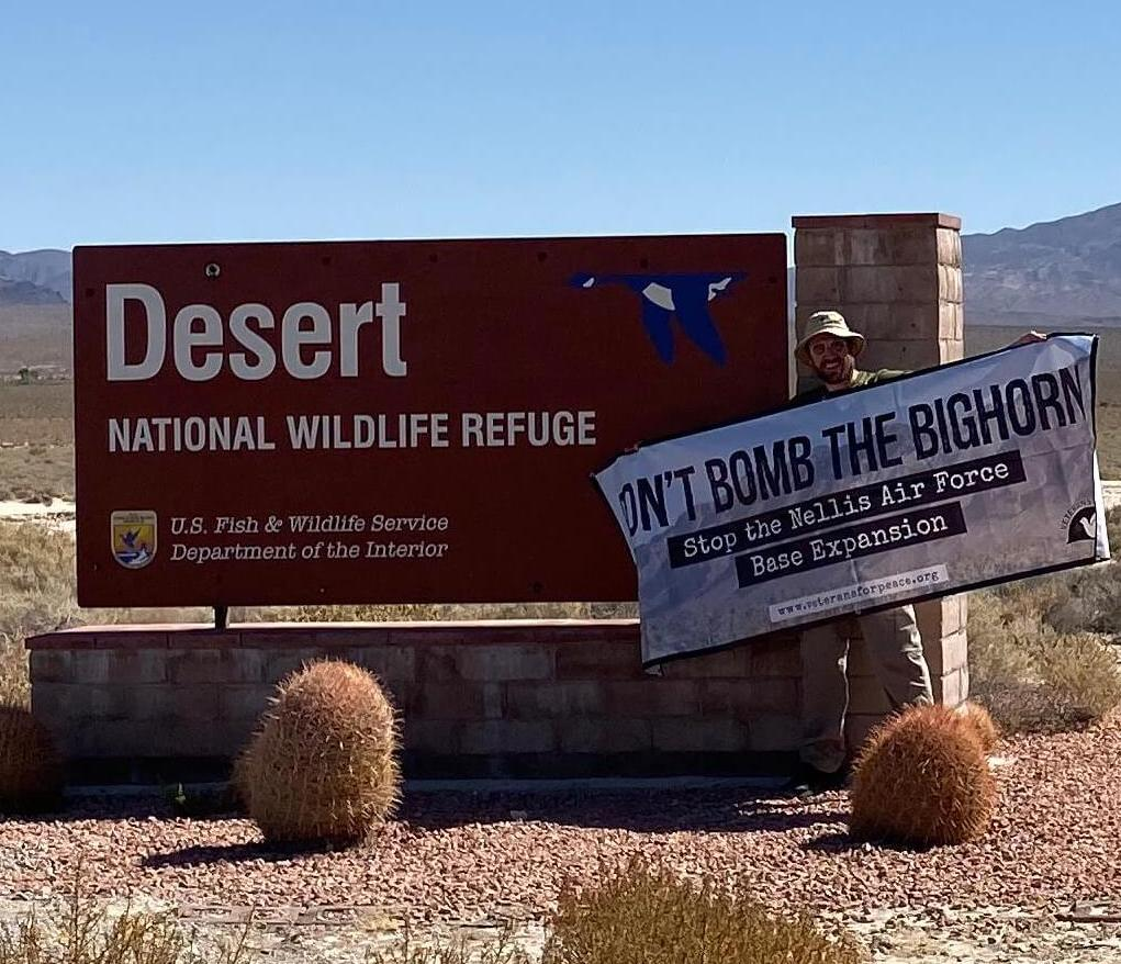 VFP Executive Director Holding Banner in front of Desert National Wildlife Refuge sign